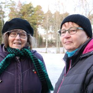 Två äldre kvinnor står på en parkering