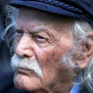 Valkohiuksinen viiksekäs Manolis Glezos katsoo kuvassa tuimasti kuvaajasta vasemmalle.