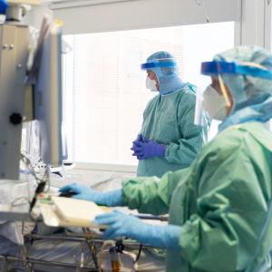 Lääkärit suojapuvuissa hoitaa potilasta.