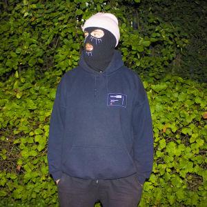 Finska snubben maskerad med skidluva framför en buske.