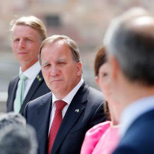 Sveriges statsminister Stefan Löfven i röd slips omgiven av andra svenska ministrar.