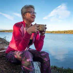 Nainen pinkissä takissa istuu kiven päällä kuksa käsissä, hymyilee, taustalla järvi ja erämaata.