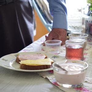 En äldre persons han på ett bord intill en frukost med juice, smörgås och yoghurt,