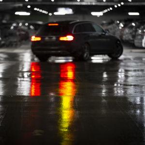 Bilar i ett mörkt och vått parkeringsgarage.