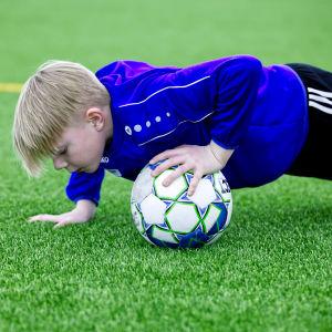 En pojke gör övningar på fotbollsträningar med blå jacka och svarta byxor.