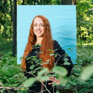 Suvi Sinervo seisoo metsän keskellä hymyillen. Hänen takanaan on sininen neliö.