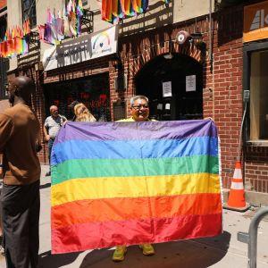 En person håller upp en regnbågsflagga utanför baren Stonewall Inn i New York.