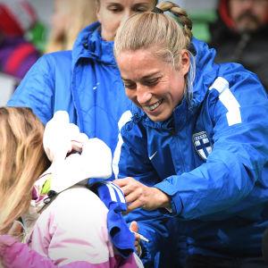 Linda Sällström skriver en autograf på en tröja på damernas fotbollslandslagsträning i Vasa 2019.