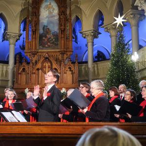 Kör sjunger klädd i svart och rött framme vid träaltaret i den i övrigt vita Johanneskyrkan. I bakgrunden julgran med stjärna i topp.