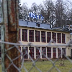 Bild på Björkboda låsfabrik taget genom ett stängsel.