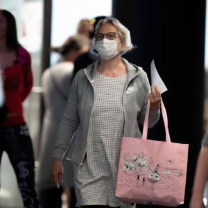 Nainen kävelee ihmisvilinässä kohti kameraa kädessään vaalenpunainen Muumi-kestokassi. Kassin kuvassa Pikku-Myy on vedessä kellumassa ja hänestä näkyy vain varpaat ja pää. Naisella on kasvoillaan suun ja nenän peittävä valkoinen hengityssuojain.