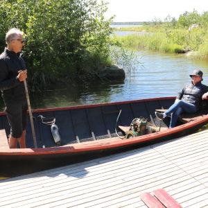 En kvinna sitter i aktern av en gammal puttputt-båt som ligger förtöjd vid en brygga. I fören står en man.