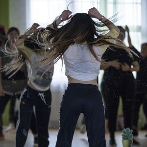 Kvinnor dansar under danslektion. Personerna är fotograferade bakifrån.