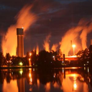Iltanäkymä tyynen veden yli kohti kaupungin siluettia.