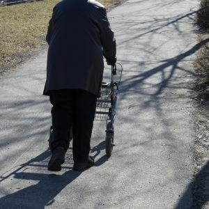 En äldre person går ute med en rullator.