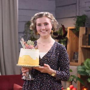hobbykonditorn Nadine Hagman håller i ett uppläggningsfat med färdiga morotstårtan