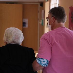 En kvinna i vårduniform och munskydd håller en äldre dam i armen.