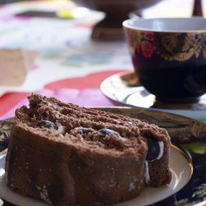 En bit rulltårta på en assiett, i bakgrunden en kaffekopp.