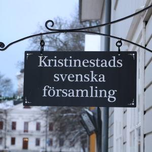 En skylt hänger från väggen. På skylten står det Kristinestads svenska församling.