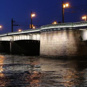Iltanäkymä virtaavan Neva-joen yli kohti jykevää kivi-metallirakenteista siltaa ja katuvaloja.
