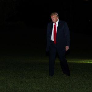 Donald Trump kävelee Valkoisen talon pihanurmella. Tausta on pimeä. Trumpilla on tumma puku ja kirkkaanpunainen kravatti.