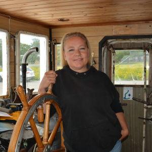 En blond kvinna står vid rodret inne i styrhytten på fartyget Suukko 2.