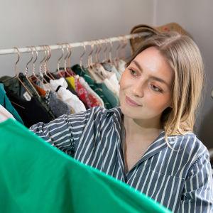 Jenni Rotonen pitää kädessään henkaria, jossa vihreä mekko.