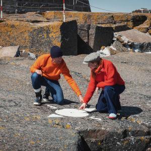 Mies ja nainen osoittavat sormillaan valkoisella maalilla kallion pintaan maalattua kompassin kuvaa.