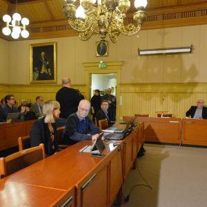 Fullmäktigeledamöter och medierepresentanter förbereder sig fusionsbeslut i Kaskö fullmäktigesal.