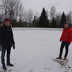 Två män står i en ishockeyrink utomhus.