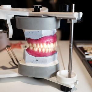 Hammasproteesi hymyilee prässissä, ympärillä yksittäisiä hampaita. Kulzer Nordicin osasto.