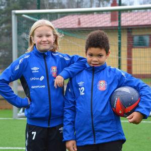 En flicka och en pojke på fotbollsplan.