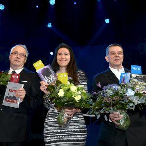 Seppo Aalto, Siiri Enoranta och Olli Jalonen står på rad med blommor och sina vinnande verk i handen.
