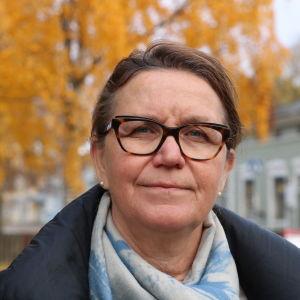 En medelålders kvinna med glasögon och brunt hår. I bakgrunden syns träd i höstskrud.