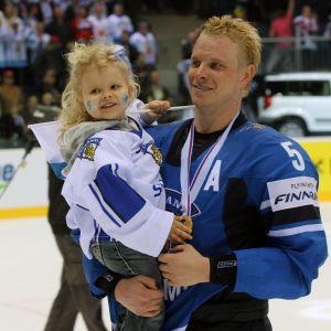 Lasse Kukkonen med sin dotter i famnen efter VM-guldet 2011.