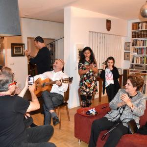 Ihmisiä illanvietossa Jussi Pakkasvirran olohuoneessa, kokoontuneena kuuntelemaan Jussi Pakkasvirran kitaransoittoa.