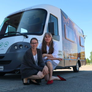Två kvinnor sitter på huk framför en husbil, sommarväder.