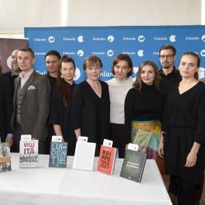 Kandidaterna för Fack-finlandiapriset 2019 står på rad bakom ett bord med deras böcker.