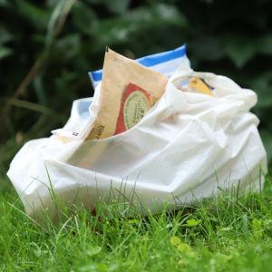 En påse med sopor på en gräsmatta.