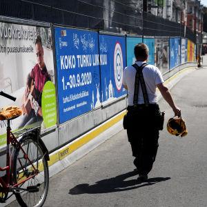 Työntekijä kantaa suojakypärää kädessään.