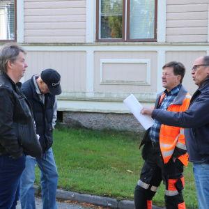Fyra män står på en gårdsplan och diskuterar.