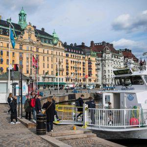 Båtresenärer kliver ombord på färja vid Nybroplan.