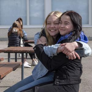 Palokan yhtenäiskoulun 7 -luokkaa käyvät ystävykset Henna ja Sofia halaavat toisiaan välitunnilla.