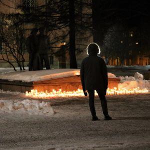 Person i vinterjacka står vid tända ljus utanför en kyrka.