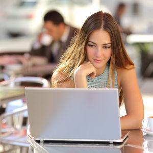 Kvinna sitter vid ett bord på ett kafe och ser ner på sin bärbara dator.