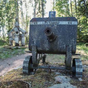 Kuvassa kaksi veistosta, etualalla vanha konekivääri, taustalla vaaleampi betoninen rakennelma, ympärillä metsää