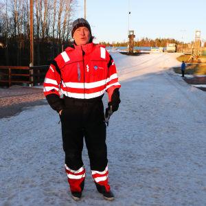 Juha Savolainen iklädd orange overall framför en ett snöigt landskap i solsken.