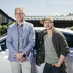 Luottomiehen Juhis (Kari Ketonen) ja Tommi (Antti Luusuaniemi) seisovat vierekkäin vaaleaan autoon nojaten kotipihassaan katsoen kameraan.