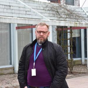 Fred Wilén står ute på gården framför Matteus kyrka.
