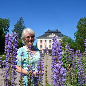 Lupiner i förgrunden, Birgitta Dahlberg och Storsarvlax gård i bakgrunden.
